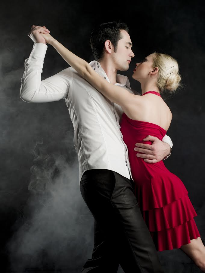 Young couple dancing on black foggy background
